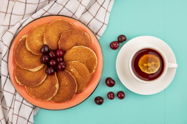 Side view of pancakes with cherries in plate on plaid cloth and cup of tea with lemon slice in it on blue background