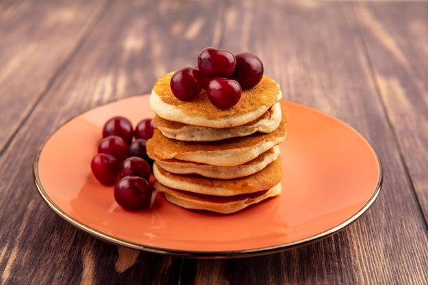 Side view of pancakes with cherries in plate on wooden background