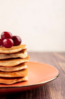 Side view of pancakes with cherries in plate on wooden surface and white background