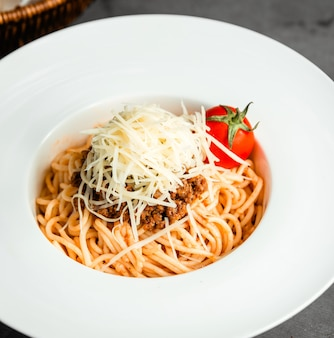 Side view of pasta with minced meat grated cheese and fresh tomato in white plate on black