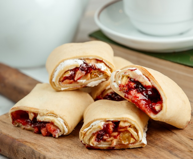 Side view of pastry roll with jam and raisins