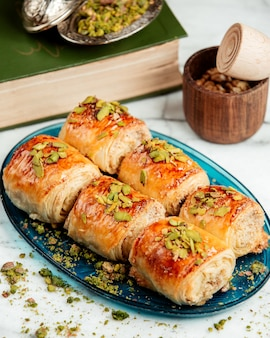 Side view of pastry rolls with pistachio on platter