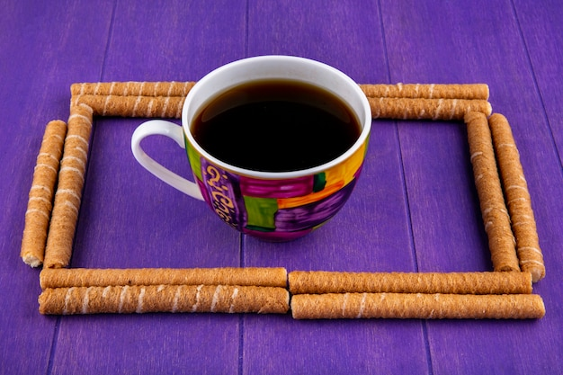 Side view of pattern of crispy sticks set in square shape with cup of coffee on center on purple background