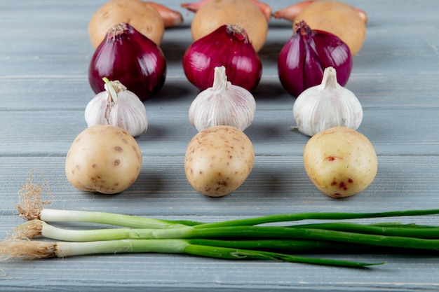 Side view of pattern of vegetables as potato onion garlic scallion on wooden background