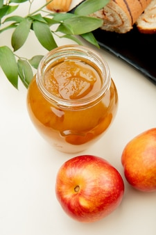 Side view of peach jam in a glass jar and fresh ripe nectarines on white