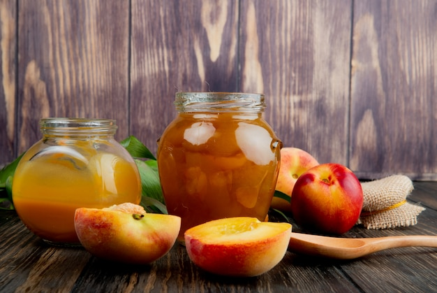 Side view of peach jam in a glass jar and fresh ripe peaches on wooden background