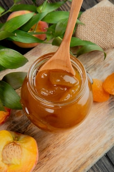 Side view of peach jam in a glass jar with wooden spoon on wooden background