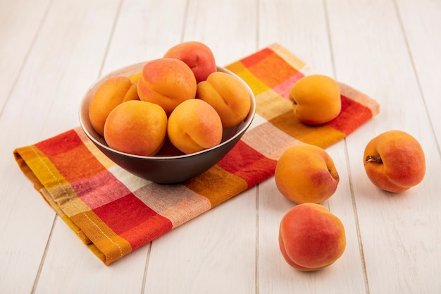 Side view of peaches in bowl on plaid cloth and on wooden background