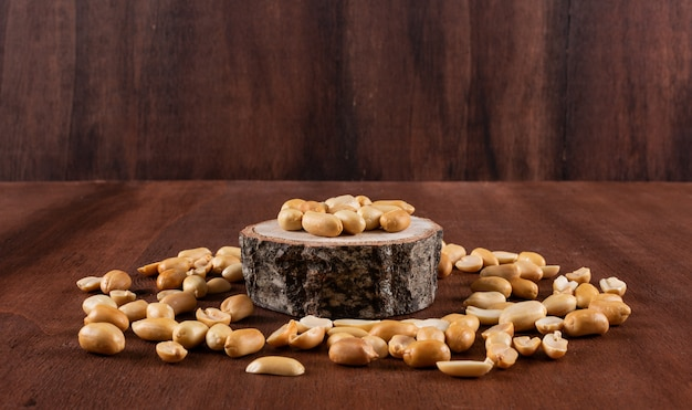 Side view peanuts on wooden stand surrounded by peanuts
