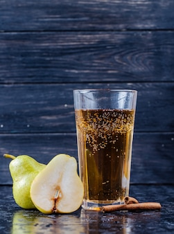 Vista laterale del succo di pera in un bicchiere con pere mature fresche a fondo di legno nero