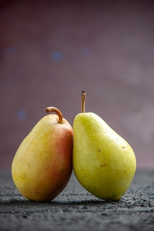 Side view pears on table two ripe green-yellow-red pears on the purple background