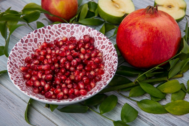 Side view of peeled pomegranate on a plate with halves of a green apple and leaf branches on a gray surface