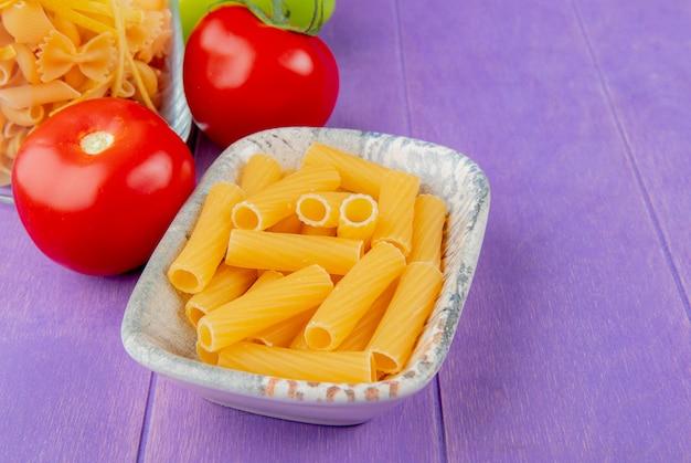 Vista laterale dei maccheroni del penne e di altri tipi in ciotole e pomodori sulla tavola porpora con lo spazio della copia