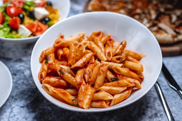 Side view penne pasta with tomato sauce salt pepper and herbs on a plate