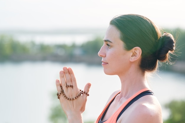 Side view of pensive young woman with hair bun holding mala beads in hands and looking into distance
