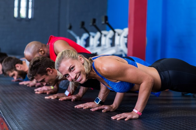 Side view of people doing push-ups in gym