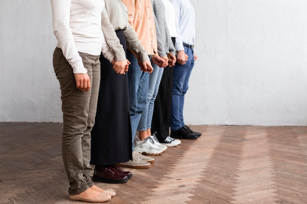 Side view of people holding hands at a group therapy session