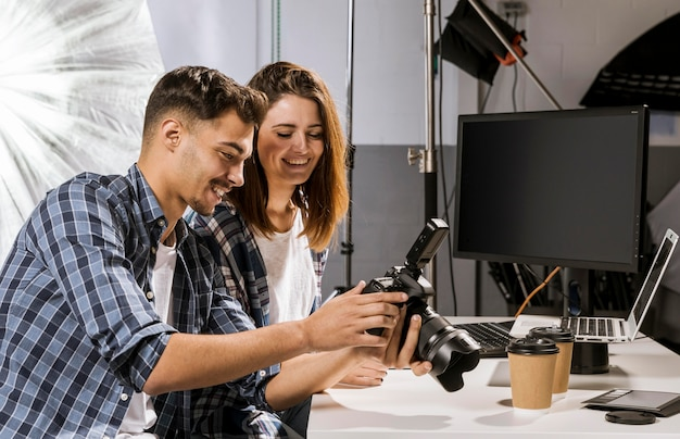 Боковой вид людей, смотрящих на фотографии на камеру
