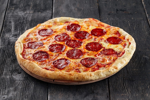 Side view on pepperoni, pizza on wooden surface