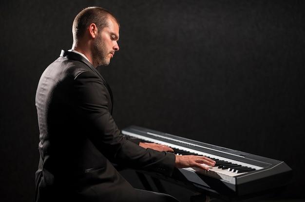 Вид сбоку человека, играющего на цифровом миди-пианино