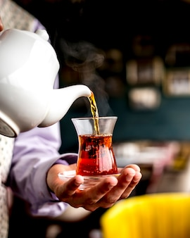 Side view of a person pouring black tea from white ceramic teapot into armudu glass