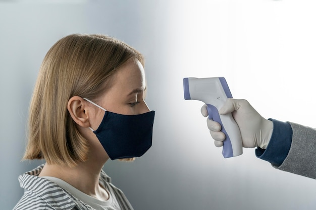Side view person taking the temperature of a woman