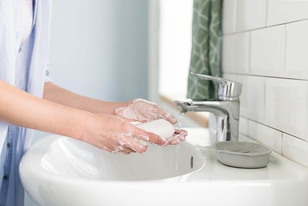 Vista laterale della persona che usando la saponetta per lavarsi le mani