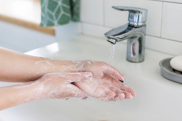 Side view of person washing hands with soap in the bathroom