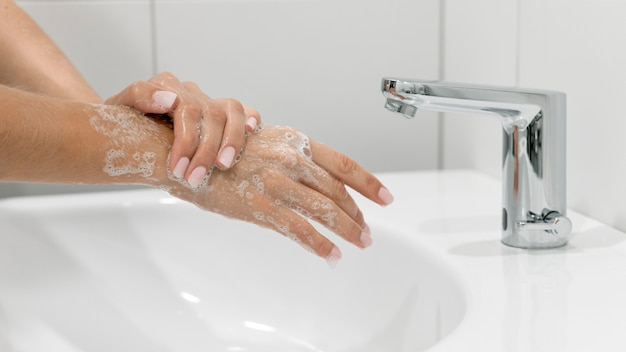 Side view person washing hands