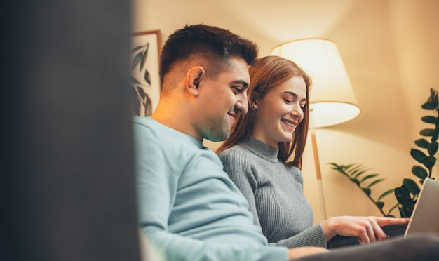 Side view photo of a caucasian couple sitting on the sofa and using a laptop in the night