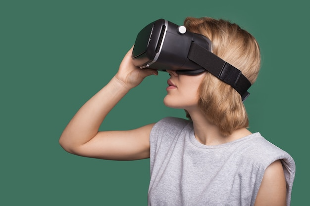 Side view photo of a caucasian woman with blonde hair trying new vr headset on a green studio wall