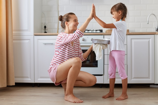 Side view photo of cheerful charming mommy and small kid giving high-five in light kitchen, baking delicious dessert together, family wearing casual style clothing, posing at home.