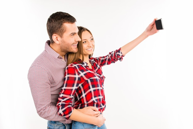 Side view photo of couple in love taking selfie
