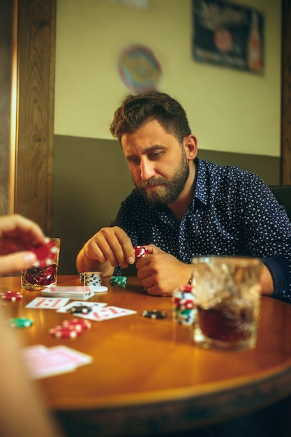 Side view photo of friends sitting at wooden table. friends having fun while playing board game.