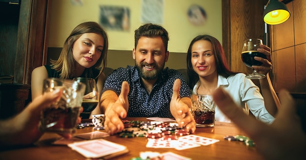 Side view photo of male and female friends sitting at wooden table. men and women playing card game. hands with alcohol close-up. poker, evening entertainment and excitement concept