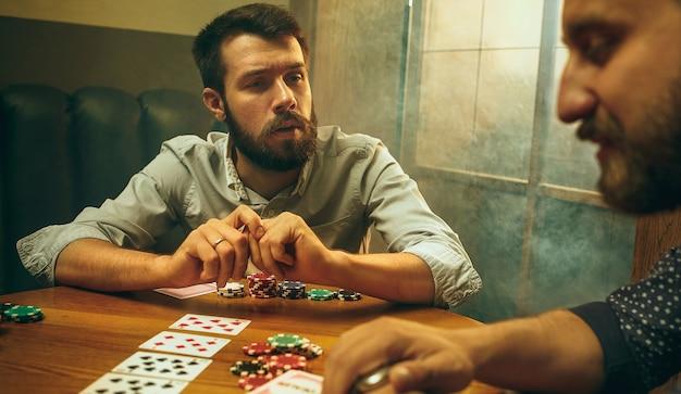 Foto di vista laterale di amici maschi e femmine seduti al tavolo di legno. uomini e donne che giocano a carte. mani con il primo piano dell'alcool.