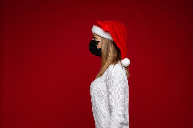 빨간색 배경에서 포즈를 취하는 동안 보호 마스크와 산타 모자를 쓰고 금발 아가씨의 측면보기 사진. 공간 복사