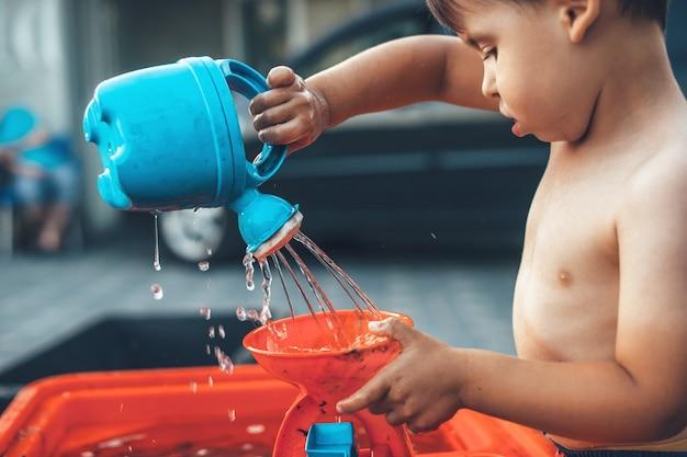 家でプラスチックのおもちゃと水で遊んでいる白人の少年の側面写真