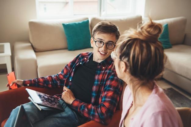 논의하는 동안 태블릿에서 집에서 일하는 안경 백인 부부의 측면보기 사진