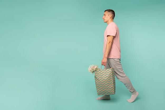 Фото уверенного молодого человека в розовой футболке, вид сбоку, с покупками и цветами в руках на синем фоне