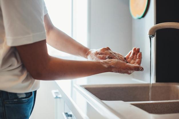비누로 부엌에서 손을 씻는 남자의 측면보기 사진