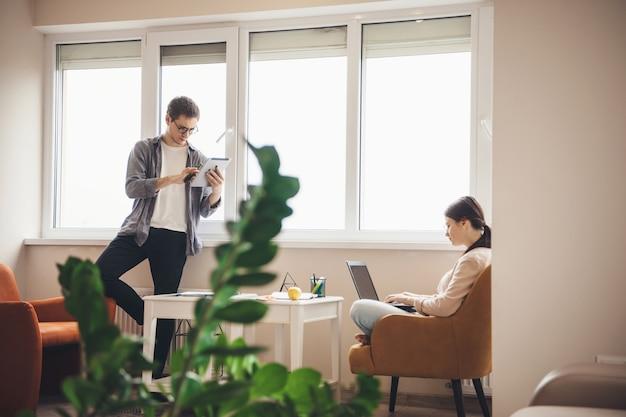 Фотография молодой бизнес-пары, удаленно работающей за ноутбуком и планшетом дома возле окна, вид сбоку
