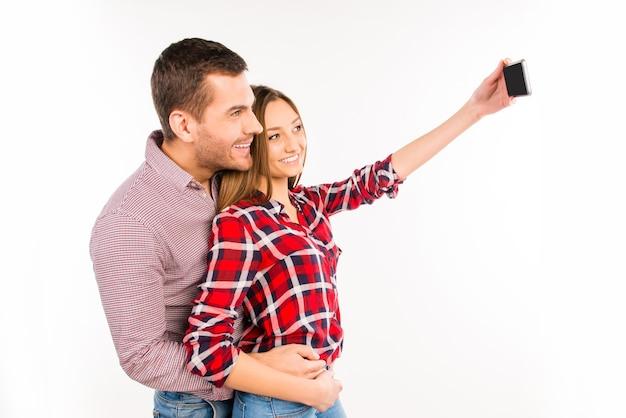 Фотография вида сбоку влюбленной пары, делающей селфи