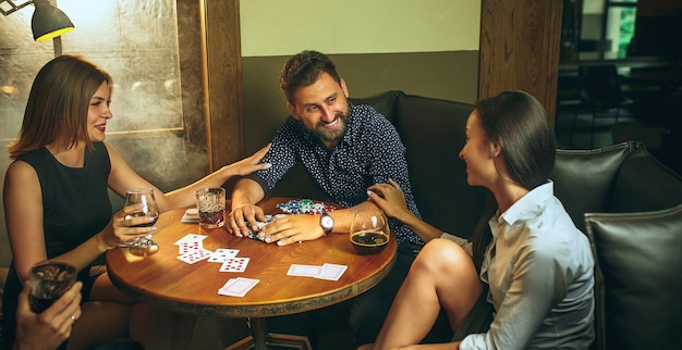 Фото вид сбоку друзей, сидящих за деревянным столом. друзья весело играют в настольную игру.