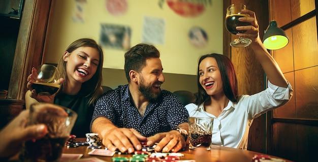 木製のテーブルに座っている男性と女性の友人の側面写真。男性と女性のトランプゲーム。アルコールのクローズアップと手。ポーカー、イブニングエンターテインメント、興奮のコンセプト