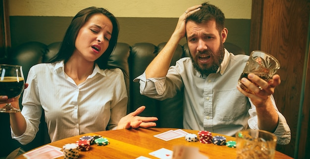 木製のテーブルに座っている男性と女性の友人の側面写真。男性と女性のトランプゲーム。アルコールのクローズアップと手。