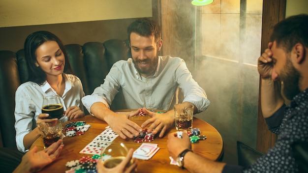 Фото вида сбоку друзей мужского и женского пола, сидящих за деревянным столом. мужчины и женщины играют в карточную игру. руки с крупным планом алкоголя.