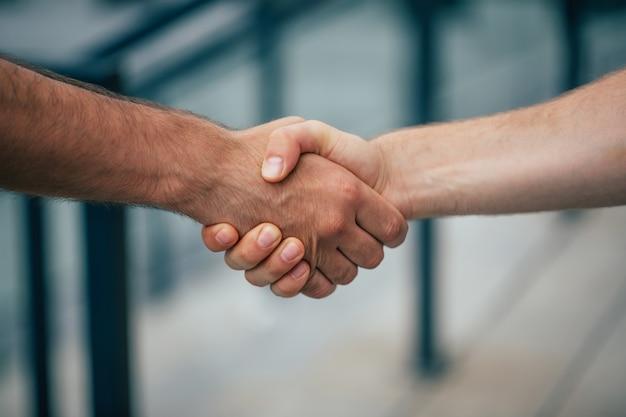 屋外での2人の男性の握手の側面写真