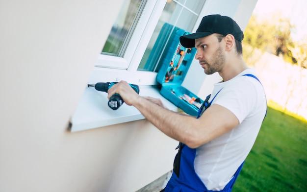 Фотография вида сбоку молодого рабочего в униформе, когда он устанавливает или ремонтирует окно на открытом воздухе