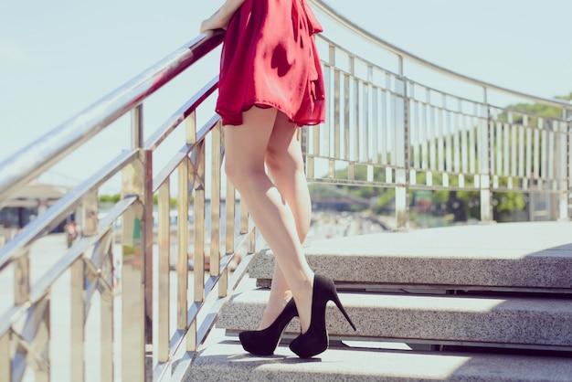 Вид сбоку фото портрет сексуального соблазнительного кроя стройные длинные ноги, красное ретро блестящее красочное шифоновое элегантное платье. счастливая девушка ждет любовника, прогулки в центре города, расслабляющий. размытый фон концепция